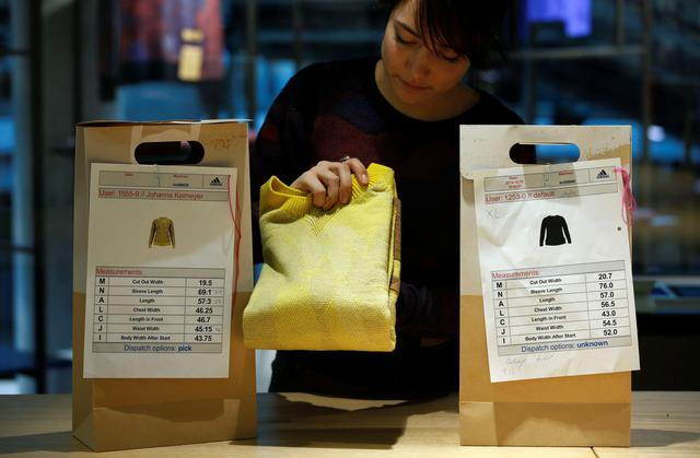 A staff member packs a knitted sweater into a customer pick up bag at the Adidas Knit for You store in Berlin, Germany March 7, 2017. Picture taken March 7, 2017.  REUTERS/Fabrizio Bensch