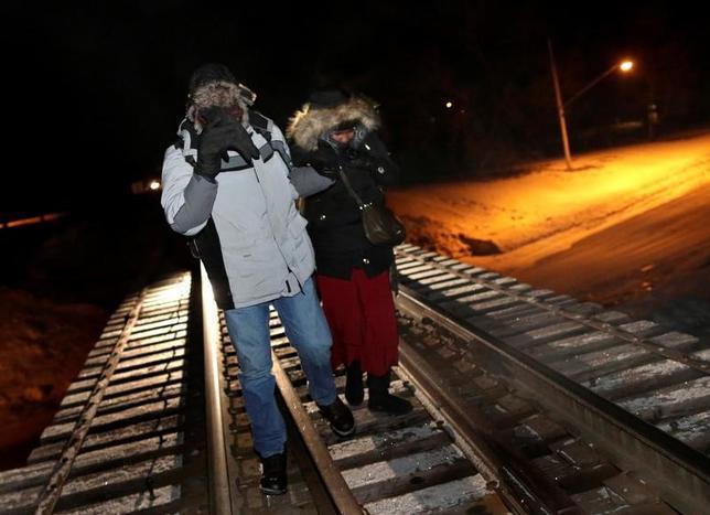 3月20日、カナダ政府が公表したデータによると、同国で1─2月に難民認定を申請した外国人は5520人に上り、昨年から大幅に増加した。写真は米国からカナダに入国するため鉄道レール上を歩く難民。カナダのマニトバ州エマーソンで2月撮影(2017年 ロイター/Lyle Stafford)