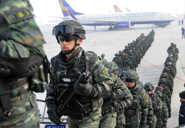 3月21日、中国の国営英字紙チャイナ・デイリーは、国内の「テロリスト下部組織」による攻撃は、治安対策の強化により減少していると報じた。ただ専門家によると、未遂件数は依然として高水準だという。写真は対テロリスト運動の一環で新疆ウイグル自治区ウルムチ市からカシュガル市に向け飛行機に乗り込む準軍事警官。2月撮影(2017年 ロイター)
