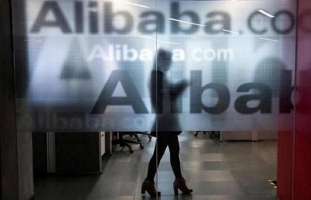 An employee is seen behind a glass wall with the logo of Alibaba at the company's headquarters on the outskirts of Hangzhou, Zhejiang province, April 23, 2014. REUTERS/Chance Chan/Files