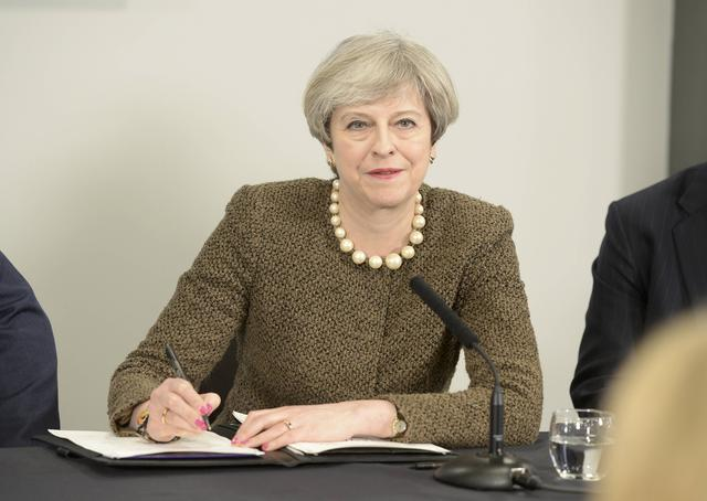 Britain's Prime Minister Theresa May signs a Swansea City deal during a meeting at the Liberty Stadium in Swansea March 20, 2017. REUTERS/Ben Birchall/Pool