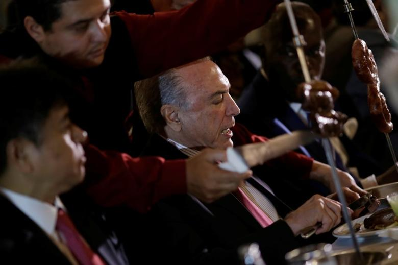 Brazil's President Michel Temer eats barbecue in a steak house after a meeting with ambassadors of meat importing countries of Brazil, in Brasilia, Brazil March 19, 2017. REUTERS/Ueslei Marcelino