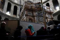 """زوار بجوار سياج حول """"القبر المقدس"""" في كنيسة القيامة بالقدس يوم الاثنين. تصوير: رونن زفولون - رويترز."""