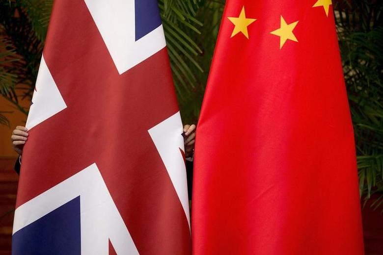 FILE PHOTO: A worker adjusts British and China (R) national flags on display for a signing ceremony at the seventh UK-China Economic and Financial Dialogue ''Roundtable on Public-Private Partnerships'' at Diaoyutai State Guesthouse in Beijing, China September 21, 2015. REUTERS/Andy Wong/Pool/File Photo