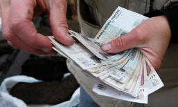 Продавец в Красноярске пересчитывает деньги. Реальная заработная плата в РФ в феврале 2017 года, по оценке Росстата, выросла на 1,3 процента как в годовом выражении, так и  к предыдущему месяцу. REUTERS/Ilya Naymushin