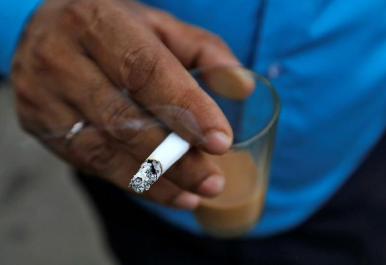 A man smokes a cigarette along a road in Mumbai, October 26, 2016. REUTERS/Danish Siddiqui/Files