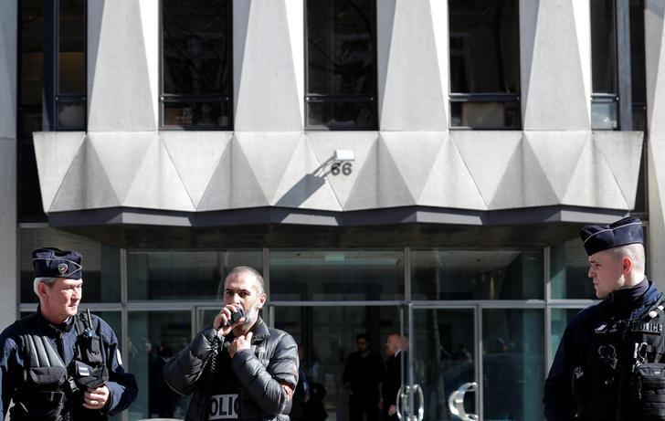Police officers stand guard in front of the main entrance of the International Monetary Fund (IMF) offices where an envelope exploded in Paris, France, March 16, 2017. REUTERS/Christian Hartmann/Files