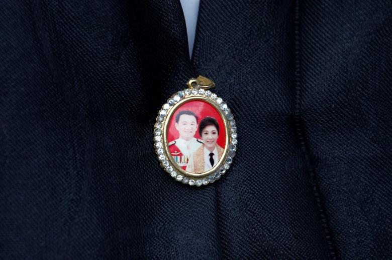 A supporter wears a locket with picture of former Thai Prime Ministers Thaksin Shinawatra and Yingluck Shinawatra, while waiting for former Prime Minister Yingluck's arrival at the Supreme Court in Bangkok, Thailand November 4, 2016. REUTERS/Chaiwat Subprasom/Files