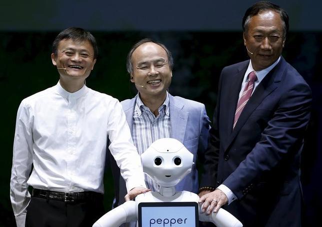 3月22日、ソフトバンクグループ社長の孫正義氏(中央)と中国電子商取引最大手のアリババ集団の創業者で会長の馬雲(ジャック・マー)氏(左)は、このままいけばぶつかり合うことになる。千葉市で2015年6月撮影(2017年 ロイター/Yuya Shino)