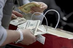 Люди пересчитывают деньги в магазине. Федрезерв начал готовить общество и рынки к росту инфляции, но не ответил на вопрос о том, как высоко она может подняться и как надолго.  REUTERS/Andrew Kelly/File Photo