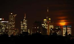 The moon is partly covered by clouds as it rises above the skyline of Frankfurt, Germany, early evening November 14, 2016. REUTERS/Kai Pfaffenbach