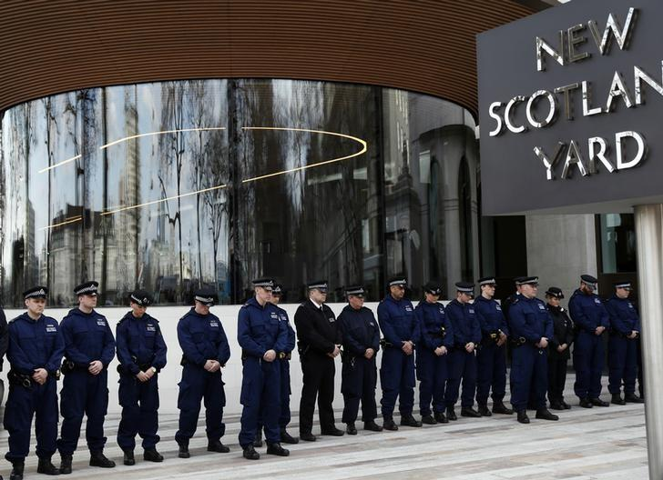 Police officers observe a moment's silence outside New Scotland Yard in Westminster the day after an attack, in London, Britain March 23, 2017. REUTERS/Stefan Wermuth