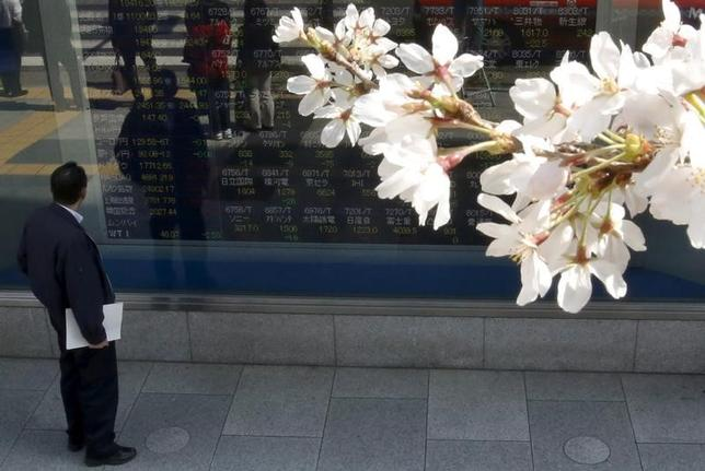 3月24日、前場の東京株式市場で、日経平均株価は前営業日比189円87銭高の1万9275円18銭となり、続伸した。写真は都内にある証券会社の株価ボード前で2015年3月撮影(2017年 ロイター/Issei Kato)