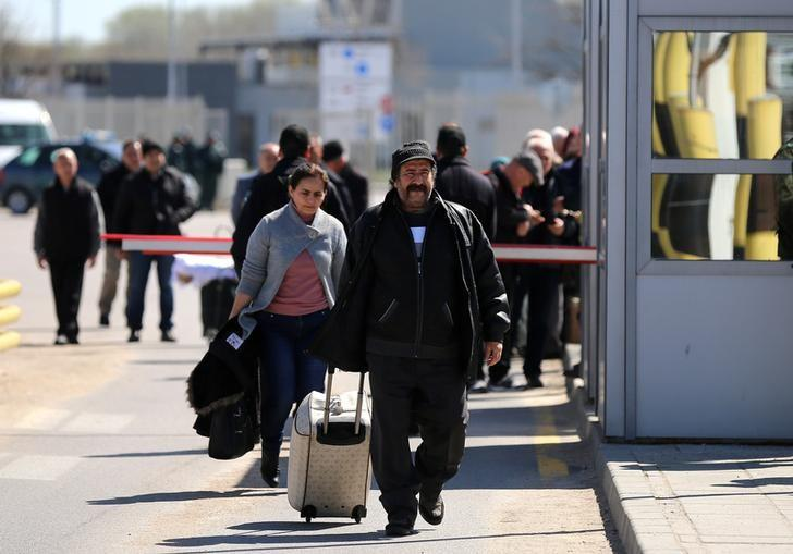 People carry their luggage as they cross the border crossing between Turkey and Bulgaria on foot during a protest at Kapitan Andreevo border checkpoint, Bulgaria March 24, 2017.  REUTERS/Stoyan Nenov