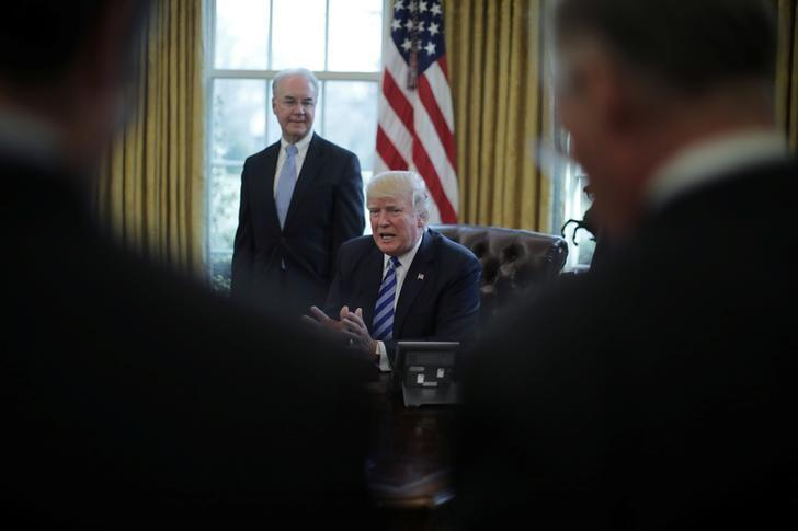 U.S. President Donald Trump talks to journalist at the Oval Office of the White House after the AHCA health care bill was pulled before a vote, accompanied by U.S. Health and Human Services Secretary Tom Price (L) and Vice President Mike Pence (not pictured), in Washington, U.S., March 24, 2017. REUTERS/Carlos Barria