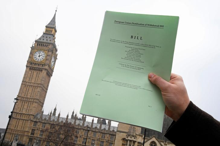 FILE PHOTO: A journalist poses with a copy of the Brexit Article 50  bill, introduced by the government to seek parliamentary approval to start the process of leaving the European Union, in front of the Houses of Parliament in London, Britain, January 26, 2017. REUTERS/Toby Melville/File Photo
