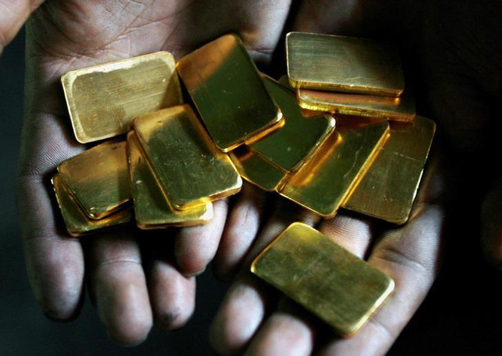 A worker shows gold biscuits at a precious metals refinery in Mumbai, India March 3, 2008.   REUTERS/Arko Datta/File Photo