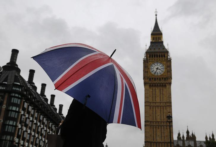 A woman holds a Union flag umbrella in front of the Big Ben clock tower (R) and the Houses of Parliament in London October 4, 2014. REUTERS/Luke MacGregor/Files