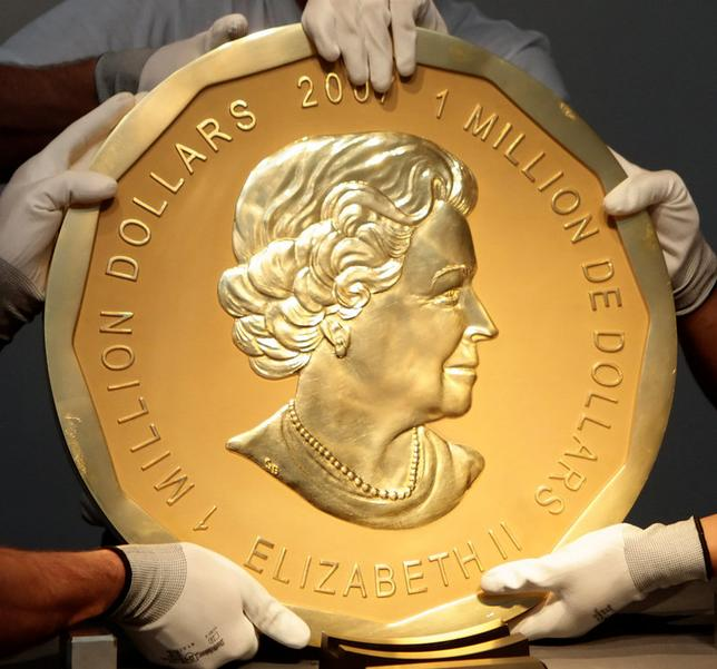 FILE PHOTO - Picture taken in Vienna, Austria on June 25, 2010 shows experts of an Austrian art forwarding company holding one of the world's largest gold coins, a 2007 Canadian $ 1,000,000 ''Big Maple Leaf''. An identical coin was stolen from Berlin's Bode Museum on March 27, 2017.     REUTERS/Heinz-Peter Bader/File Photo