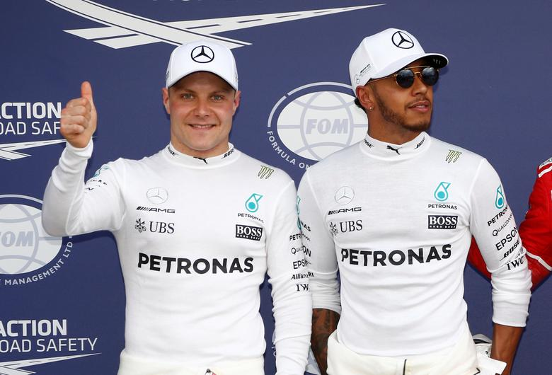 Formula One - F1 - Australian Grand Prix - Melbourne, Australia - 25/03/2017 Mercedes drivers Valtteri Bottas (L) of Finland and Lewis Hamilton (C) of Britain react after qualifying.       REUTERS/Brandon Malone