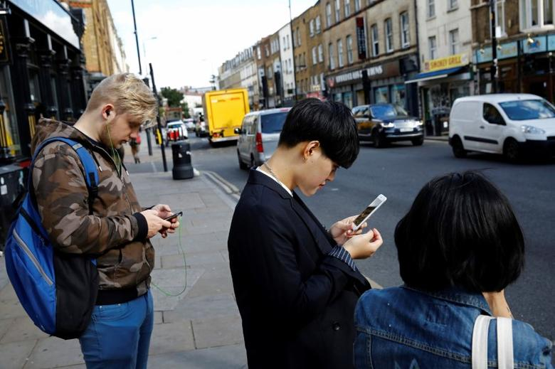 Pedestrians look at their phones near Brick Lane in London. REUTERS/Stefan Wermuth