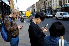 Pedestrians look at their phones near Brick Lane in London. REUTERS/Stefan Wermuth
