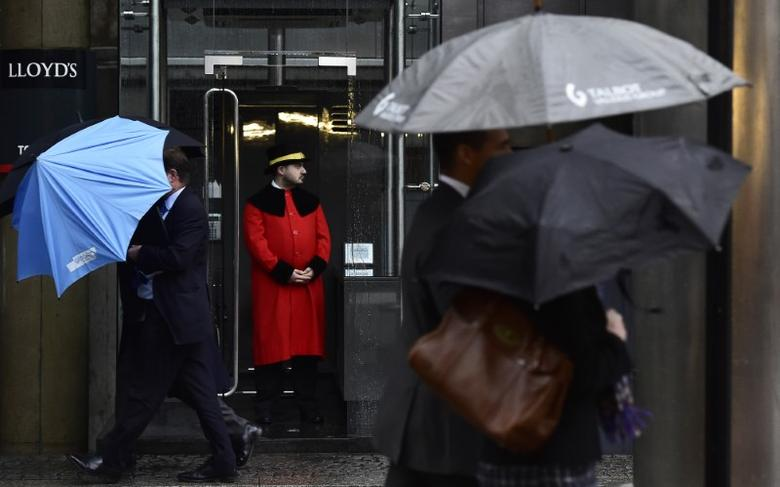 A doorman looks out as workers walk in the rain past the Lloyd's of London building in the City of London, Britain, January 7, 2016. REUTERS/Toby Melville/Files