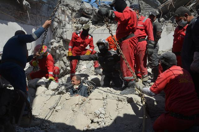 Iraqi firefighters look for bodies buried under the rubble, of civilians who were killed after an air strike against Islamic State triggered a massive explosion in Mosul, Iraq March 27, 2017.  REUTERS/Stringer