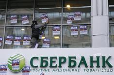 Мужчина расклеивает листовки на отделении Сбербанка в Киеве 2 февраля 2017 года. Национальный банк Киргизии (НБКР) сохранил учетную ставку на уровне 5,00 процента, сообщил Нацбанк во вторник. REUTERS/Valentyn Ogirenko