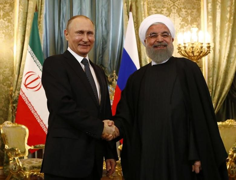 Russian President Vladimir Putin shakes hands with Iranian President Hassan Rouhani during their meeting at the Kremlin in Moscow, Russia March 28, 2017. REUTERS/Sergei Karpukhin