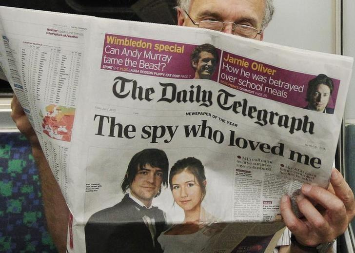 A passenger reads the Daily Telegraph newspaper, featuring a front page interview with the ex-husband of accused Russian spy Anna Chapman, on the underground in London July 2, 2010. REUTERS/Luke MacGregor/Files