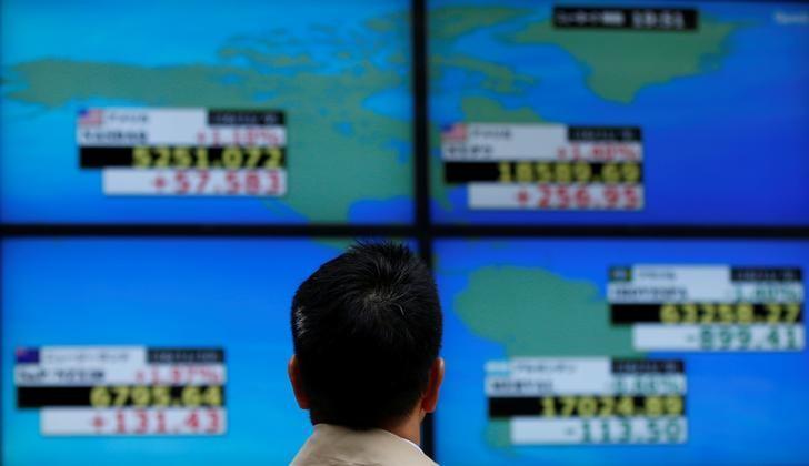 资料图片:2016年11月,东京一家券商机构外,一名男子盯着电子显示屏上的股票信息。REUTERS/Toru Hanai