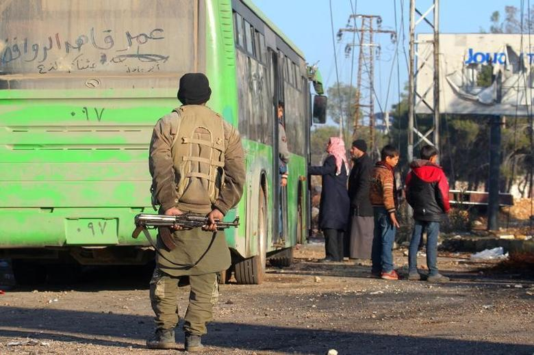 FILE PHOTO: A rebel fighter stands with his weapon near evacuees from the Shi'ite Muslim villages of al-Foua and Kefraya as they ride bueses in insurgent-held al-Rashideen, Syria December 20, 2016. REUTERS/Ammar Abdullah