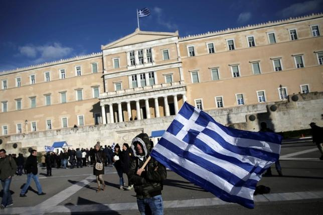 FILE PHOTO:A farmer waves a Greek national flag in front of the parliament building during a demonstration to demand tax reductions and compensation, in Athens, Greece February 14, 2017. REUTERS/Alkis Konstantinidis/File Photo