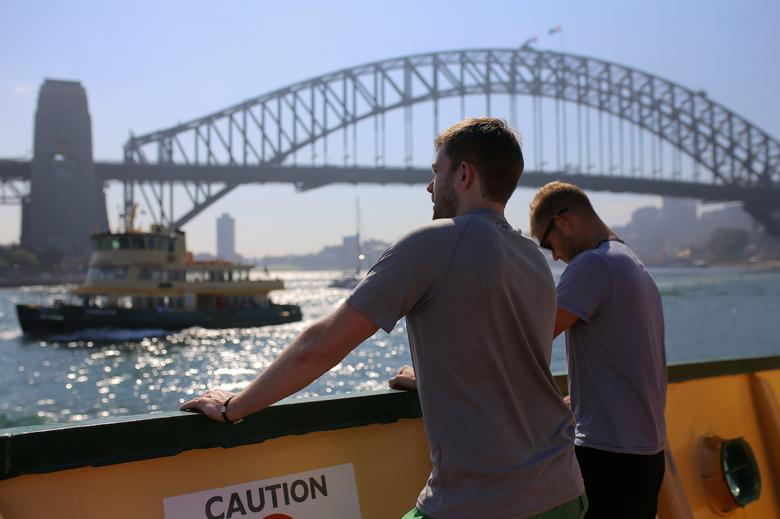 Two passengers aboard a ferry look at the Sydney Harbour Bridge as they approach Circular Quay in Sydney, Australia, March 29, 2017.     REUTERS/Steven Saphore