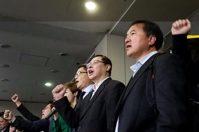 Former pro-democracy lawmaker Lee Wing-tat (R), Occupy Central movement founders Benny Tai (2nd R) and Chan Kin-man (3rd R), along with others being charged, chant slogans outside a court in Hong Kong, China March 30, 2017.  REUTERS/Venus Wu