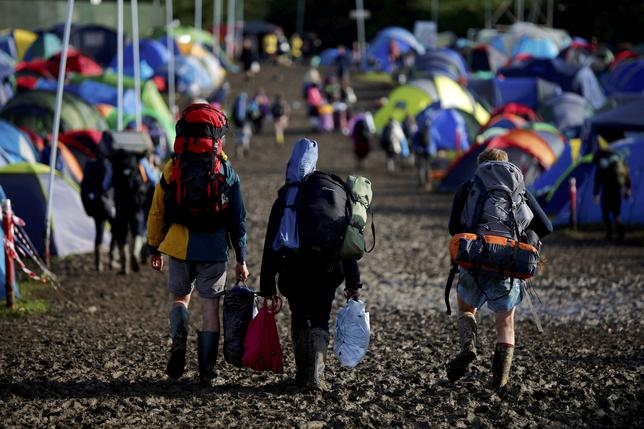 Revellers carry their belongings as they leave Worthy Farm in Somerset after the Glastonbury Festival, Britain, June 27, 2016. REUTERS/Stoyan Nenov/Files