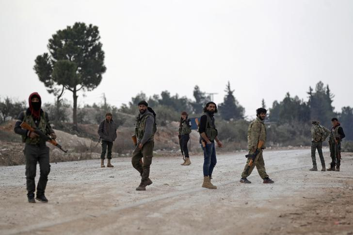 Free Syrian Army fighters carry their weapons on the outskirts of al-Bab, February 2017.   REUTERS/Khalil Ashawi
