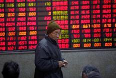 Инвестор в брокерской конторе в Шанхае. 3 января 2017 года. Шанхайские акции прервали в пятницу четырехдневную череду снижений, но показали наибольший недельный спад с середины декабря на фоне ухудшения аппетита инвесторов к риску из-за беспокойства по поводу нехватки ликвидности и ограничений на инвестиции в недвижимость. REUTERS/Aly Song