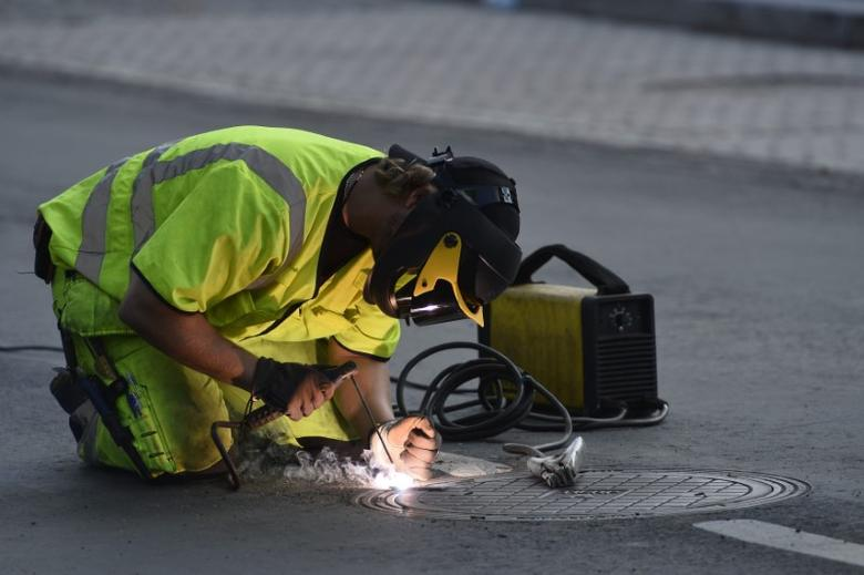 A Stockholm City worker welds shut a manhole cover in Stockholm, before U.S. President Barack Obama's visit to Sweden, September 3, 2013. REUTERS/Anders Wiklund/Scanpix Sweden
