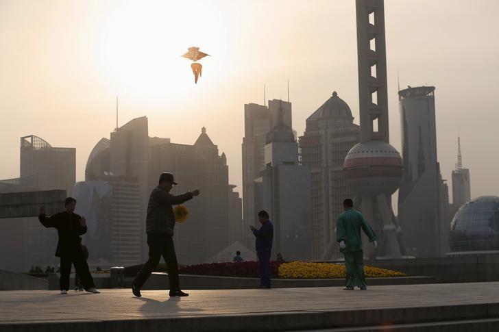 资料图片:2016年3月,上海陆家嘴金融区对面外滩地区晨练的市民。REUTERS/Aly Song
