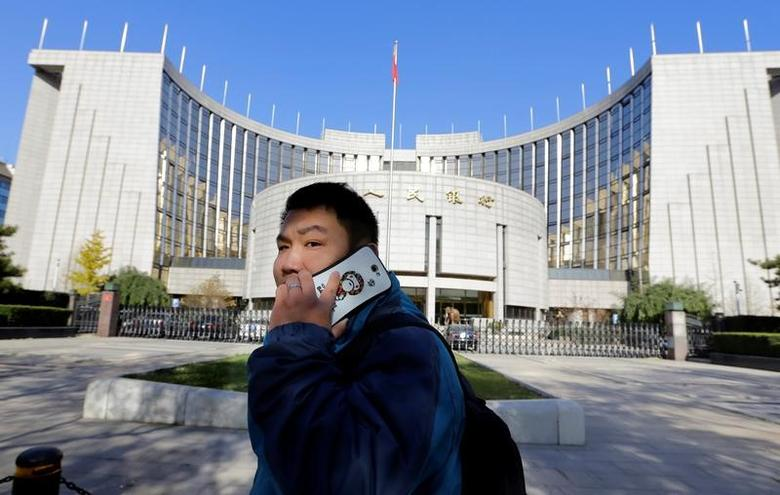 A man uses his mobile phone while walking past the headquarters of the People's Bank of China (PBOC), the central bank, in Beijing, November 20, 2013.      REUTERS/Jason Lee/File Photo