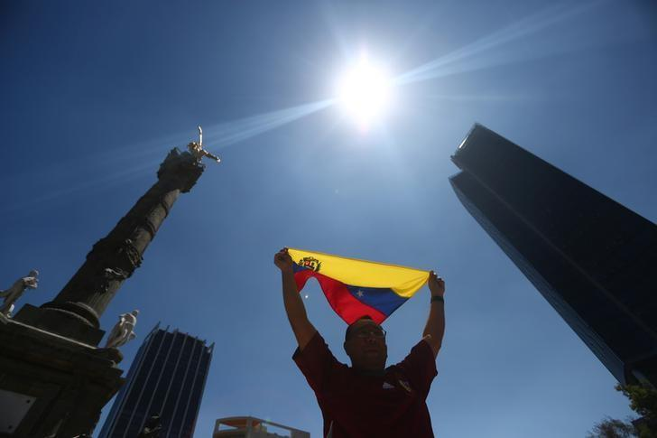 A Venezuelan living in Mexico holds a flag in a demonstration against Venezuelan President Nicolas Maduro's government at Angel de la Independencia monument in Mexico City, Mexico, April 2, 2017. REUTERS/Edgard Garrido