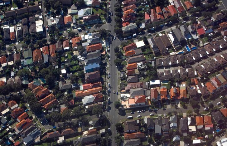 Cars travel along a road between homes in the Sydney suburb of Coogee in Australia, July 26, 2016. REUTERS/David Gray/Files