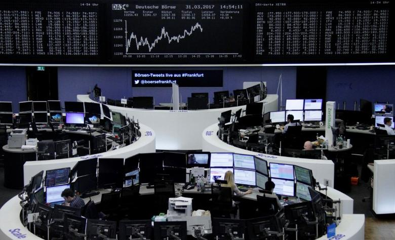 Traders work at their desks in front of the German share price index, DAX board, at the stock exchange in Frankfurt, Germany, March 31, 2017. REUTERS/Staff/Remote