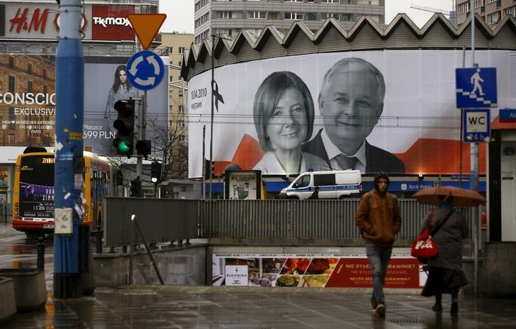 People walk in front of a giant picture of late Polish president Lech Kaczynski and his wife Maria, who died six years ago when a Polish government plane crashed in Smolensk, Russia, hanging on a building in the centre of Warsaw, Poland April 10, 2016.   REUTERS/Kacper Pempel/File Photo
