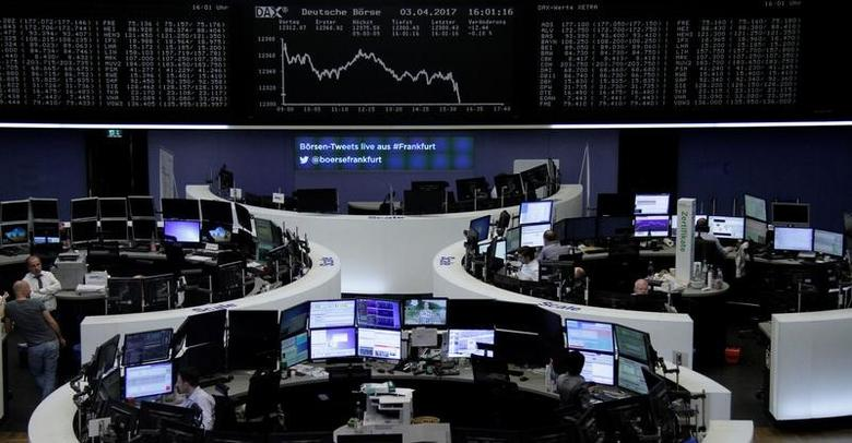 Traders work at their desks in front of the German share price index, DAX board, at the stock exchange in Frankfurt, Germany, April 3, 2017. REUTERS/Staff/Remote
