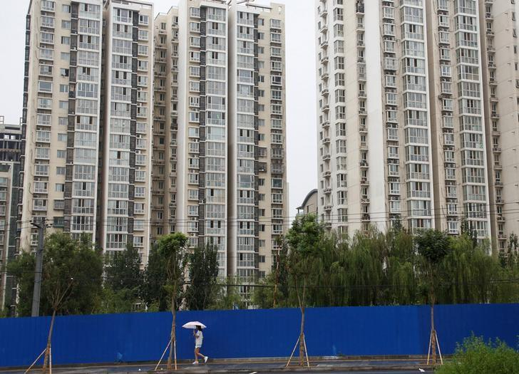 FILE PHOTO: A woman walks past residential buildings in Beijing, July 15, 2016.  REUTERS/Thomas Peter/File Photo