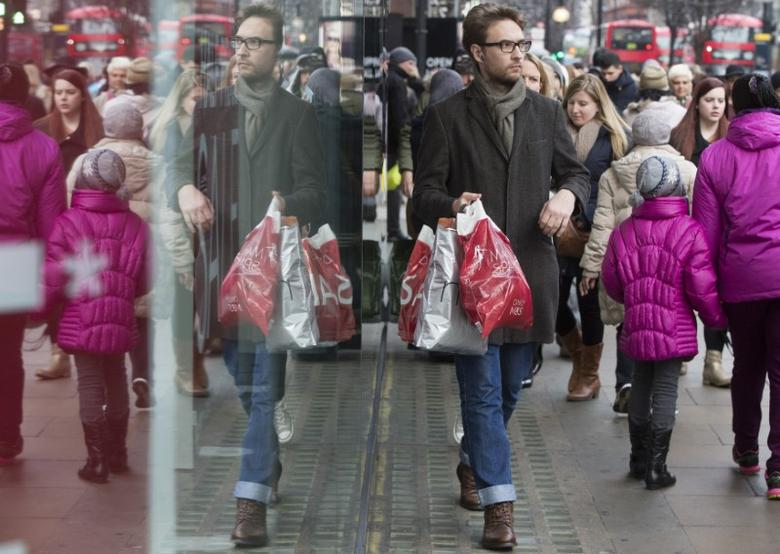 A shopper is reflected in a store window on Oxford Street in central London December 30, 2014. REUTERS/Neil Hall