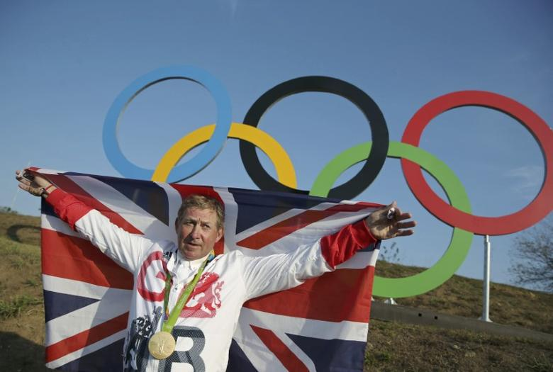 2016 Rio Olympics - Equestrian - Victory Ceremony - Jumping Individual Victory Ceremony - Olympic Equestrian Centre - Rio de Janeiro, Brazil - 19/08/2016. Gold medalist Nick Skelton (GBR) of Britain poses with his national flag in front of the Olympic rings. REUTERS/Pilar Olivares